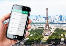 Hållande smartphone för hand med stadshandboken i Paris Fotografering för Bildbyråer