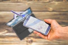 Hållande smartphone för hand på det suddiga flygflygplanet Arkivbilder