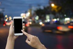 Hållande smartphone för hand på suddighetsbakgrundstransport Arkivfoto
