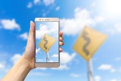 Hållande smartphone för hand som tar bild det slingriga vägmärket Royaltyfri Bild