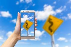 Hållande smartphone för hand som tar bild det slingriga vägmärket Arkivbild