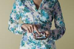 Hållande smartphone för kvinna Shoppa online-websiten Royaltyfria Bilder