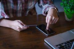 Hållande smartphone för kvinnahand` s och användakreditkort för direktanslutet royaltyfria bilder