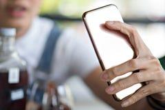 Hållande smartphone för kvinnahand för socialt online-liv royaltyfria foton