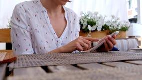 Hållande smartphone för kvinnlig hand, i ett kafé eller en restaurang stock video