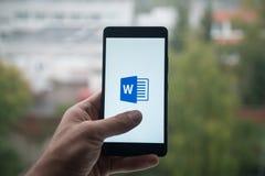 Hållande smartphone för man med logo för budbärare för ord för Microsoft kontor med fingret på skärmen Arkivbild