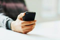 Hållande smartphone för manlig hand Fotografering för Bildbyråer