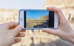 Hållande smartphone för par med den Colosseo bilden från inre Romantisk tur till Rome Royaltyfri Bild