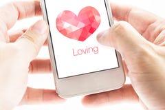 Hållande smartphone för två hand med rosa polygonhjärtaform och Lo Royaltyfria Bilder