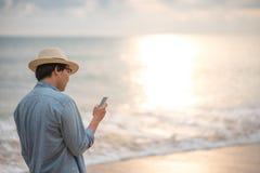 Hållande smartphone för ung man på stranden Royaltyfri Fotografi