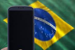 Hållande smartphone med den brasilianska flaggan Arkivbild