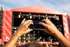 Hållande smartphones för man, i händer och att fotografera Ta fotoet på främre etapp på summet Fotografering för Bildbyråer