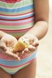 Hållande snäckskal för flicka på stranden Arkivfoto