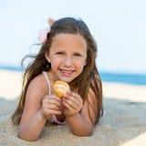 Hållande snäckskal för söt flicka på stranden. royaltyfri foto