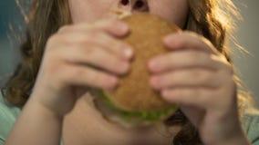 Hållande snabbmathamburgare för fet flicka med båda händer och att tugga den, framsidacloseup stock video