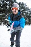 Hållande snowboard för attraktiv man och gå till freeriden till moen Arkivbild