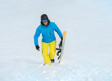 Hållande snowboard för lycklig man arkivbilder