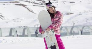 Hållande snowboard för nätt ung asiatisk kvinna stock video