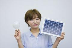 Hållande solpanel för ung kvinna och ljus kula Royaltyfria Bilder