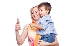 Hållande son för moder med smartphonen arkivbilder