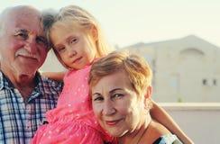 Hållande sondotter för farfar och för farmor royaltyfri foto