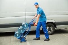 Hållande spårvagn för leveransman med vattenflaskor Royaltyfri Foto