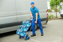 Hållande spårvagn för leveransman med vattenflaskor royaltyfria foton