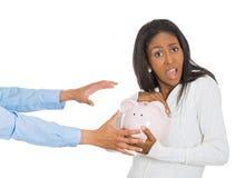 Hållande spargris för kvinna, frustrerat försöka att skydda hennes besparingar arkivfoto