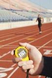 Hållande stoppur för hand med löparen på loppspår Arkivfoto