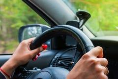 Hållande styrninghjul för kvinna, drev bilen Royaltyfri Foto