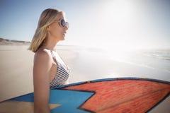 Hållande surfingbräda för kvinna på stranden Royaltyfria Foton