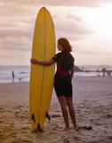 Hållande surfingbräda för ung kvinna Arkivbild