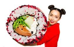 Hållande sushi för ung härlig kvinna arkivbild