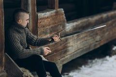 Hållande svärd för modig krigare nära historisk wood slottbyggnad Royaltyfria Foton