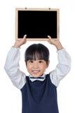 Hållande svart tavla för asiatisk kinesisk liten grundskola för barn mellan 5 och 11 årflicka Fotografering för Bildbyråer