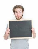 Hållande svart tavla för förvånad stilig man som isoleras på vit bakgrund Fotografering för Bildbyråer