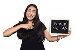 Hållande svart tavla för kvinna med textsvart fredag arkivbild