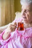 Hållande te för hög kvinna royaltyfri bild
