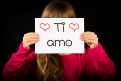 Hållande tecken för barn med den italienska ordsi Amo - jag älskar dig Royaltyfri Fotografi