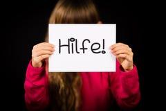 Hållande tecken för barn med det tyska ordet Hilfe - hjälp Royaltyfri Fotografi