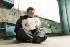 Hållande tecken för fattig affärsman som frågar för jobb arkivfoto