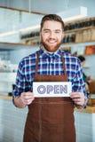 Hållande tecken för gladlynt stilig kafeteriaarbetare som är öppet i kafé Fotografering för Bildbyråer