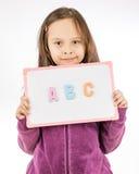 Hållande tecken för ung flicka med abc Arkivbild