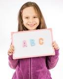 Hållande tecken för ung flicka med abc Royaltyfri Fotografi