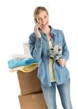 Hållande tejp för kvinna, medan genom att använda telefonen mot staplade Bo royaltyfri fotografi