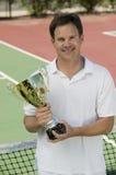 Hållande tennistrofé för man som är netto på tennisbanaståenden Arkivfoton