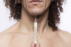 Hållande termometer för man arkivfoton