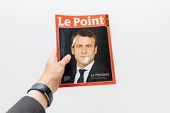 Hållande tidning för man med Emmanuel Macron på den första sidaräkningen Arkivbild