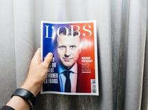 Hållande tidning för man med Emmanuel Macron på den första sidaräkningen Arkivfoton