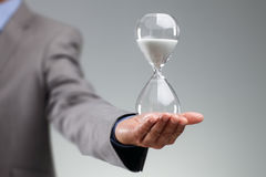 Hållande timglas för affärsman Arkivbild